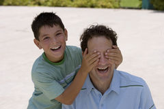 Boy (10-12) placing hands over father's eyes, laughing, portrait.  royalty free stock images