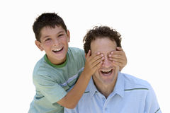 Boy placing hands over father's eyes, laughing, portrait, cut out.  royalty free stock images