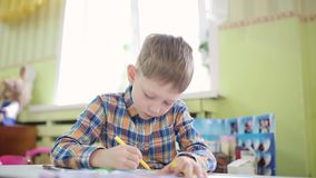 A boy in a plaid shirt draws with a yellow felt-tip pen. The student performs the task in a preschool.
