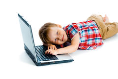 Boy in a plaid shirt with a laptop on a white background. Stock Images