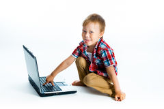 Boy in a plaid shirt with a laptop on a white background. Royalty Free Stock Image