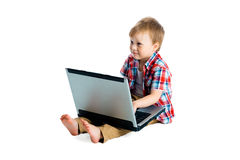 Boy in a plaid shirt with a laptop on a white background. Royalty Free Stock Photography