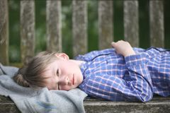 A boy in a plaid shirt lies in the garden Stock Photography