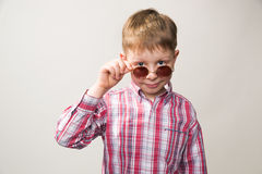 Boy in plaid shirt and sunglasses smiling Stock Image