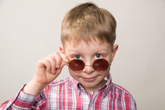 Boy in plaid shirt and sunglasses smiling Royalty Free Stock Photos