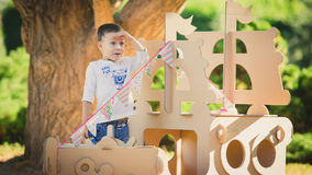 Boy plaing in a cardboard boat Stock Photography