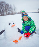 Boy plaing in the snow. Little boy having fun in the snow - making snow penguin Royalty Free Stock Photography