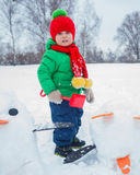 Boy plaing in the snow. Little boy having fun in the snow - making snow penguin Stock Photo