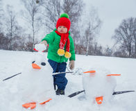 Boy plaing in the snow. Little boy having fun in the snow - making snow penguin Stock Image