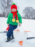 Boy plaing in the snow. Little boy having fun in the snow - making snow penguin Royalty Free Stock Photo