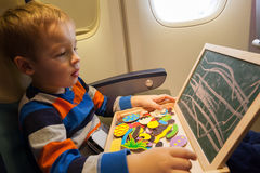 Boy in the plane drawing on board with chalk Stock Images