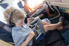 Boy in the plane. Little boy playing at tablet waiting in the plane, family vacation Stock Images