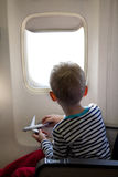 Boy in the plane. Little boy sitting inside the plane and playing with his toy plane Stock Photography