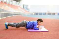 Boy plank. Slim athletic Blue jacket Asian boy doing planking exercise in the stadium during the sunrise Royalty Free Stock Image