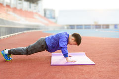 Boy plank. Slim athletic Blue jacket Asian boy doing planking exercise in the stadium during the sunrise Royalty Free Stock Photography