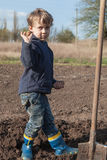 Boy planting potatoes in garden Stock Photos