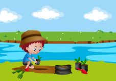 Boy planting tree by the river Royalty Free Stock Photo