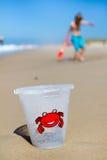 Boy and plastic bucket on beach Stock Photos