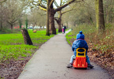 Boy on a plastic car. Little boy riding on a plastic car toy on a path in a park in autumn Stock Images