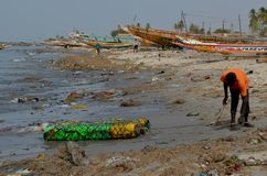 A beach covered by plastic litter in the Petite Côte of Senegal, Western Africa. A boy in a plastic litter-covered beach on Senegal`s Petite Côte, Western stock photo