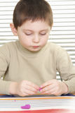 Boy with plasticine Royalty Free Stock Images