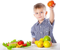 A boy and the plate of vegetables and fruits Royalty Free Stock Image