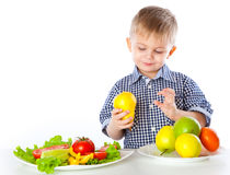 A boy and plates of vegetables and fruit Royalty Free Stock Photo