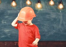 Boy play as builder or architect. Child dreaming about future career in architecture or building. Kid boy in orange hard royalty free stock image