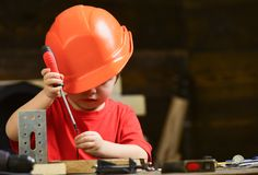 Boy play as builder or repairer, work with tools. Childhood concept. Kid boy in orange hard hat or helmet, study room royalty free stock photos