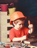 Boy play as builder or repairer, work with tools. Kid boy in orange hard hat or helmet, study room background. Childhood stock photos