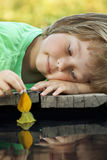 Boy play with autumn leaf ship in water, chidren in park play wi. Th boat in river Stock Photos