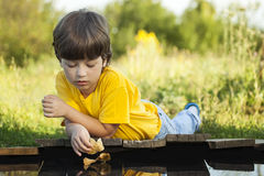 Boy play with autumn leaf ship in water, chidren in park play wi. Th boat in river Stock Photo