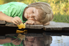 Boy play with autumn leaf ship in water, chidren in park play wi. Th boat in river Royalty Free Stock Photography