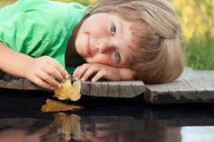 Boy play with autumn leaf ship in water, chidren in park play wi. Th boat in river Royalty Free Stock Image