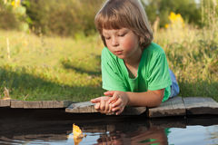 Boy play with autumn leaf ship in water, chidren in park play wi. Th boat in river Stock Photography