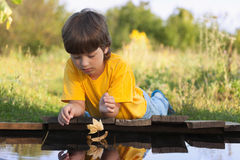 Boy play with autumn leaf ship in water, chidren in park play wi. Th boat in river Royalty Free Stock Photo