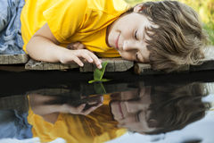 Boy play with autumn leaf ship in water, children in park play w Stock Images