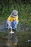 Boy play with autumn paper ship in water, chidren in park play w Stock Photos