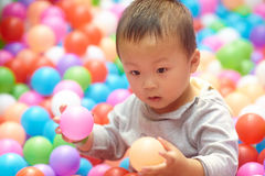 Boy play with balls. Active boy play with lots of colorful balls Stock Photo