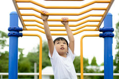 Boy play with bar. Young asian boy hang the yellow bar by his hand to exercise at out door playground Stock Image