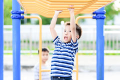 Boy play with bar. Young asian boy hang the yellow bar by his hand to exercise at out door playground Stock Photos