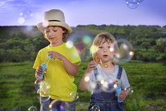 Boy play in bubbles. Outdoors Stock Images