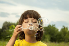 Boy play in bubbles Royalty Free Stock Photos