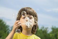 Boy play in bubbles Stock Photos