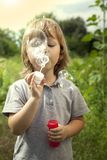 Boy play in bubbles in sunny summer day.  Stock Photography