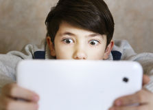 Boy play computer game. Preteen handsome boy with bad gaming habit play computer game on his tablet close up portrait stock photography