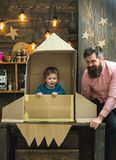Boy play with dad, father, little cosmonaut sit in rocket made out of cardboard box. Child cute boy play cosmonaut stock photo