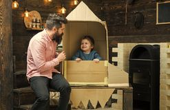 Boy play with dad, father, little cosmonaut sit in rocket made out of cardboard box. Kid happy sit in cardboard hand. Made rocket. Child boy play cosmonaut stock image