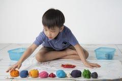 Boy play dough. A boy plaing colorful dough on white background Stock Photography