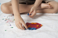 Boy play dough. A boy plaing colorful dough on white background Royalty Free Stock Images